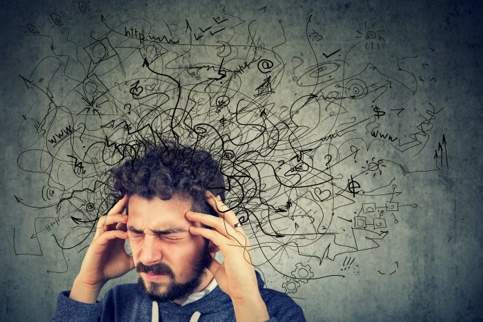 man holding head having bad thoughts thoughts are depicted with doodles