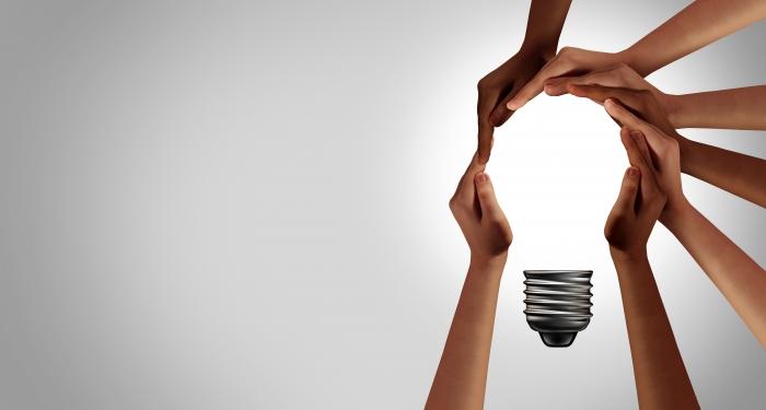 six hands forming a lightbulb together