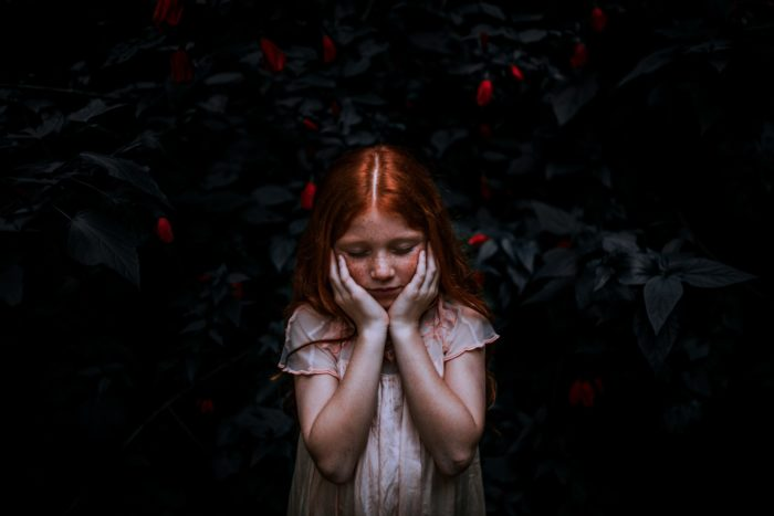 red headed child holding their head in their hands