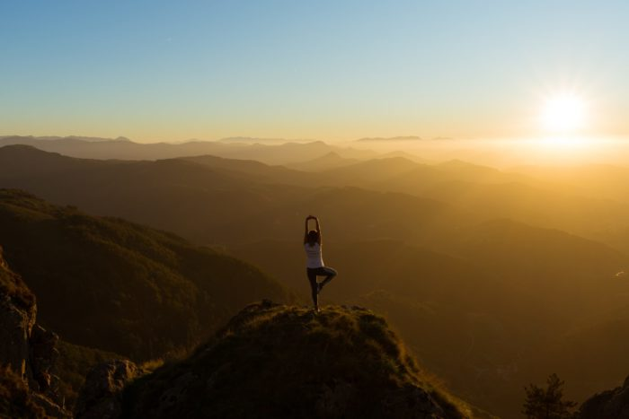 person standing on the mountain doing a yoga pose while overlooking the sunset