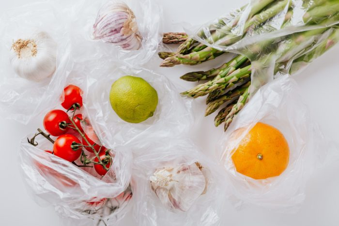 fruit and vegetables in plastic bags on a white table