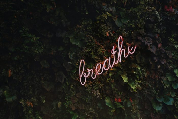 pink breathe sign written in cursive is against leaves