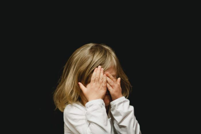 child surrounded by a black background and covering their face