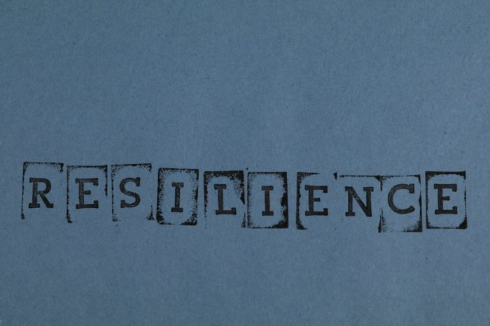 Resilience in stamp letters against a dark teal background