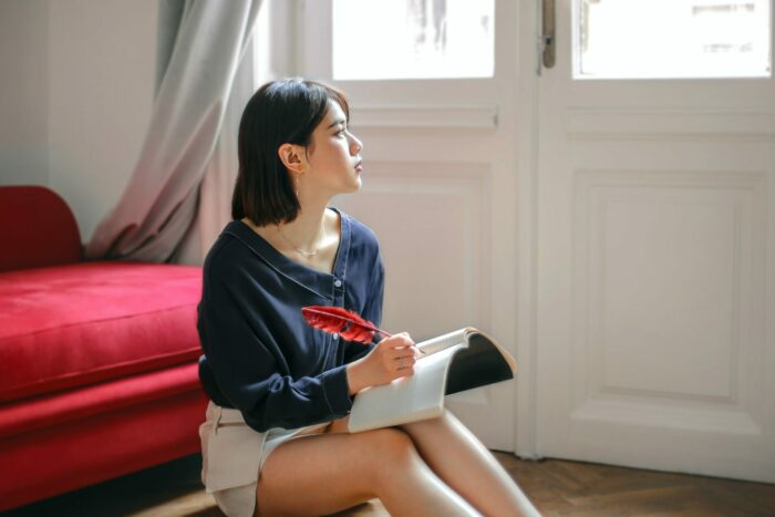 person writing in journal with a feather pen and gazing out the window