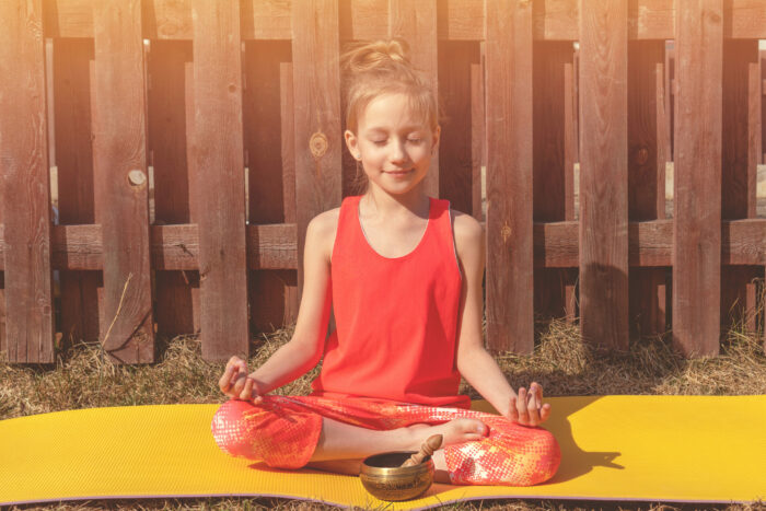 A teenager girl in an orange tracksuit is meditating in the courtyard of her house. The sun is shining. Singing bowl for meditation