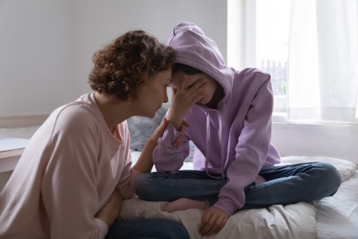 Worried mom comforting depressed teen daughter crying at home
