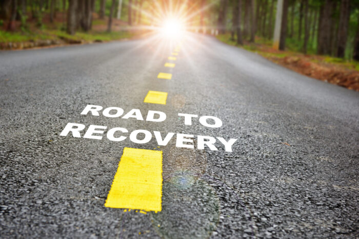 Road to recovery written on a gravel road that's in the direction of a sunbeam