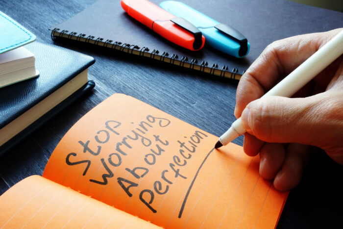 Stop Worrying About Perfection written on a notebook with orange pages