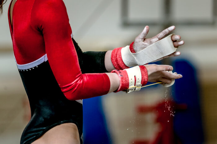 Gymnast putting chalk on grips before performing on horizontal bar