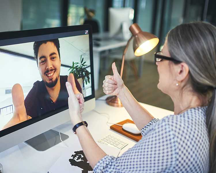 A therapist gives a thumbs-up to her online client