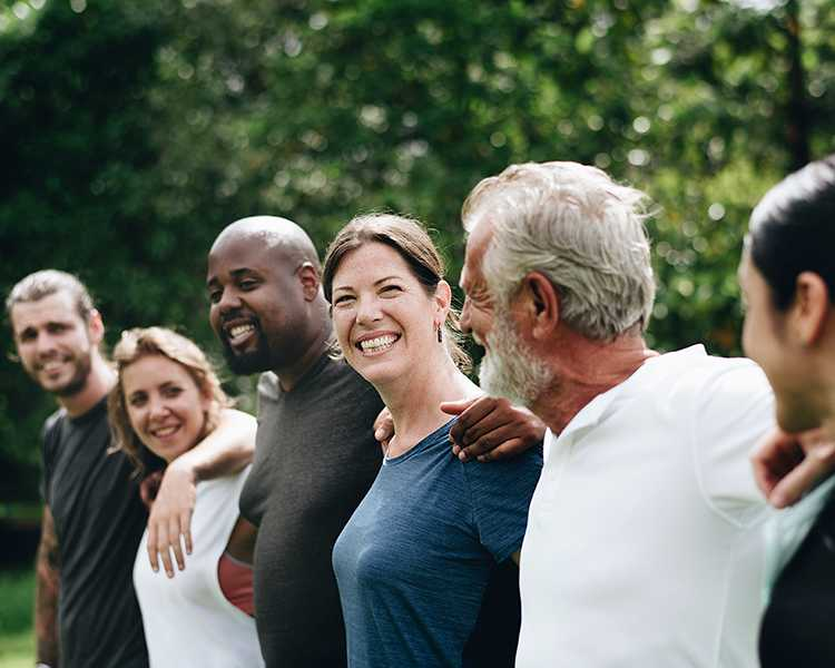 Six people outdoors touching shoulders are smiling
