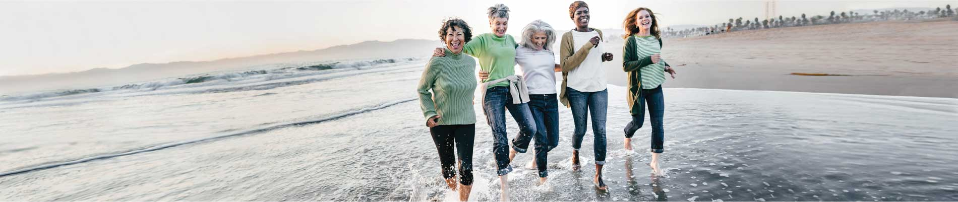 Five women laughing and kicking the water on the beach